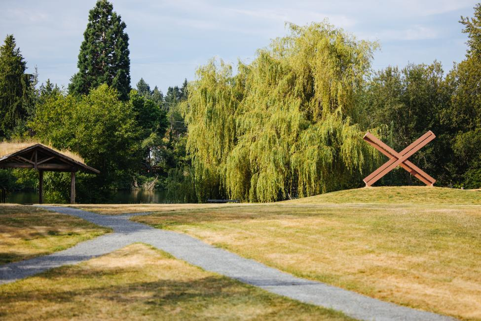 A picnic shelter, walking path and the 'Kiss' sculpture (a painted steel sculpture that looks like an X) are pictured in Ronald Bog Park.