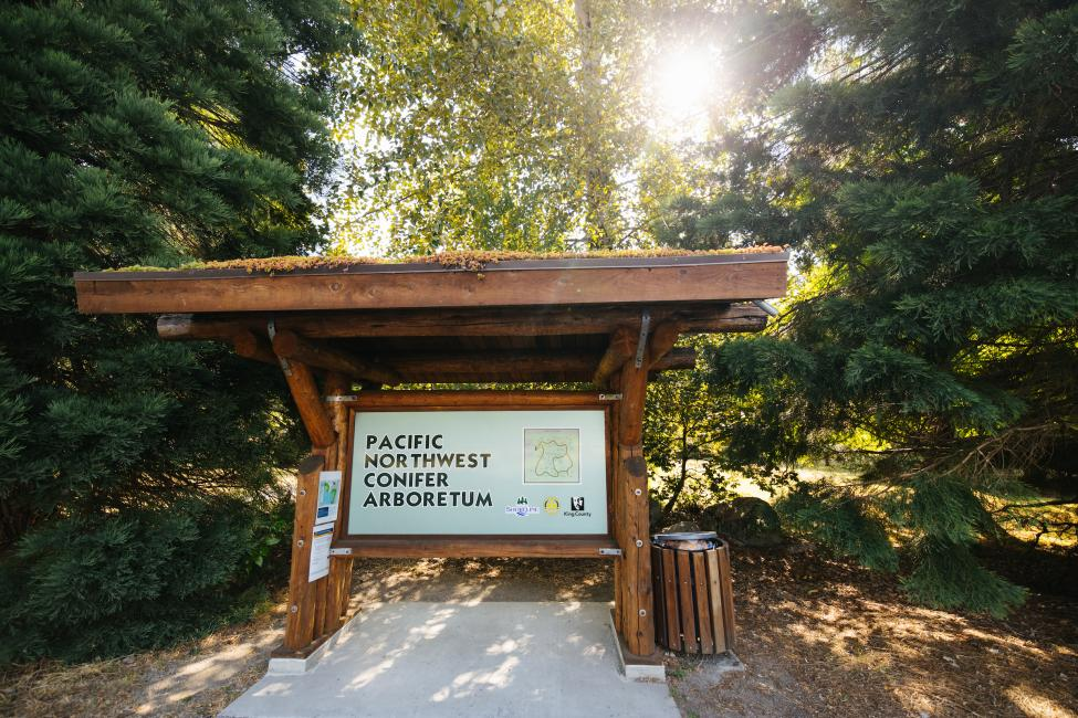 A large sign reads 'Pacific Northwest Conifer Arboretum.'