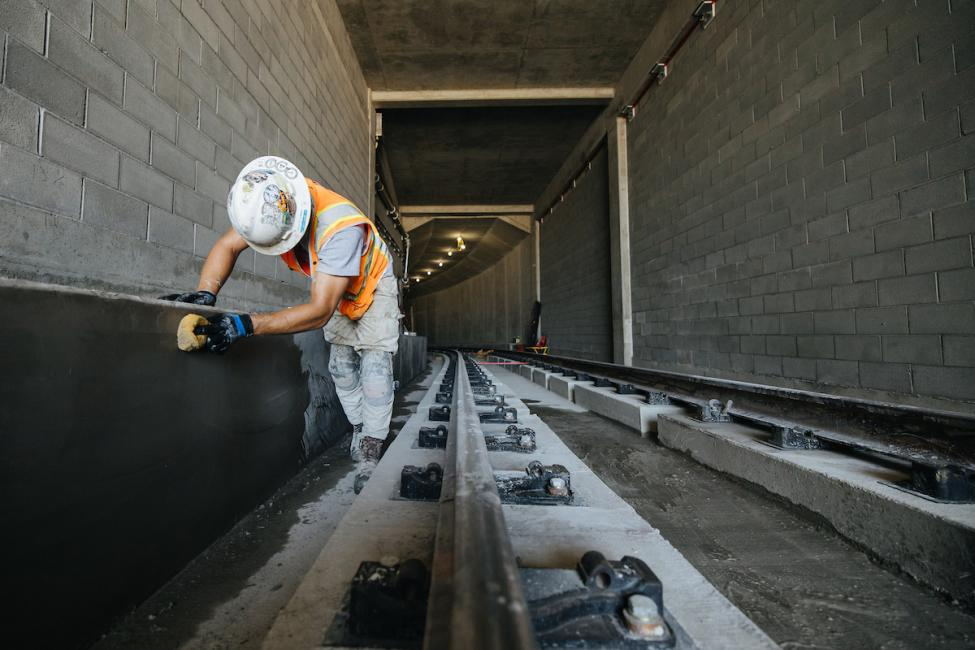 A Mason smoothing the concrete along one of the maintenance/emergency walkways inside the new Bellevue tunnel.