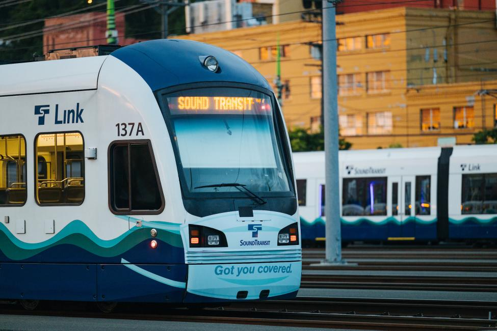 A link light rail train with a mask decal on the front.