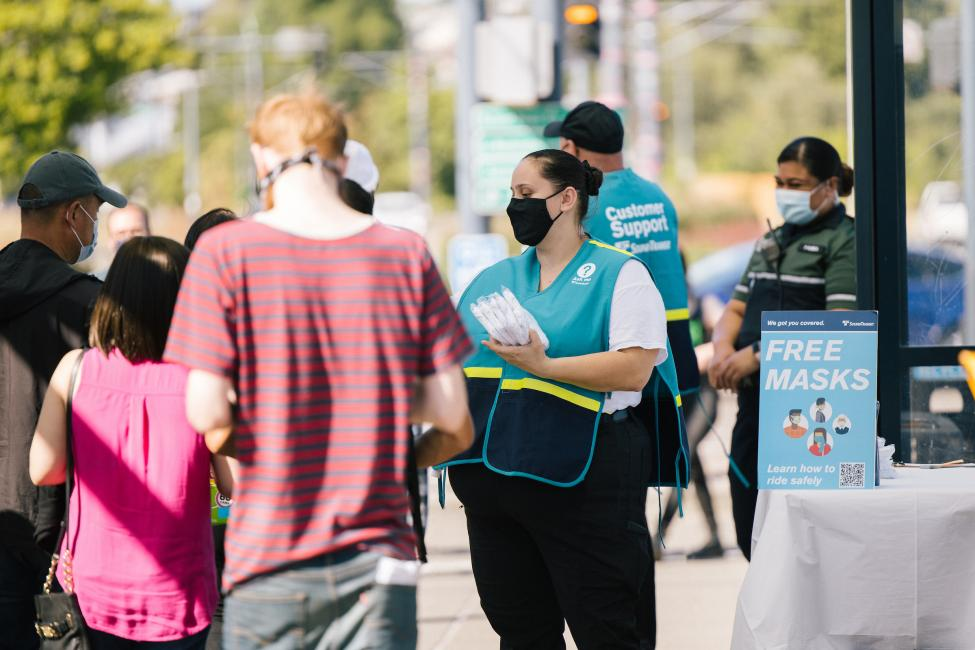 Ambassadors give away free reusable cloth masks at Rainier Beach Station in August.