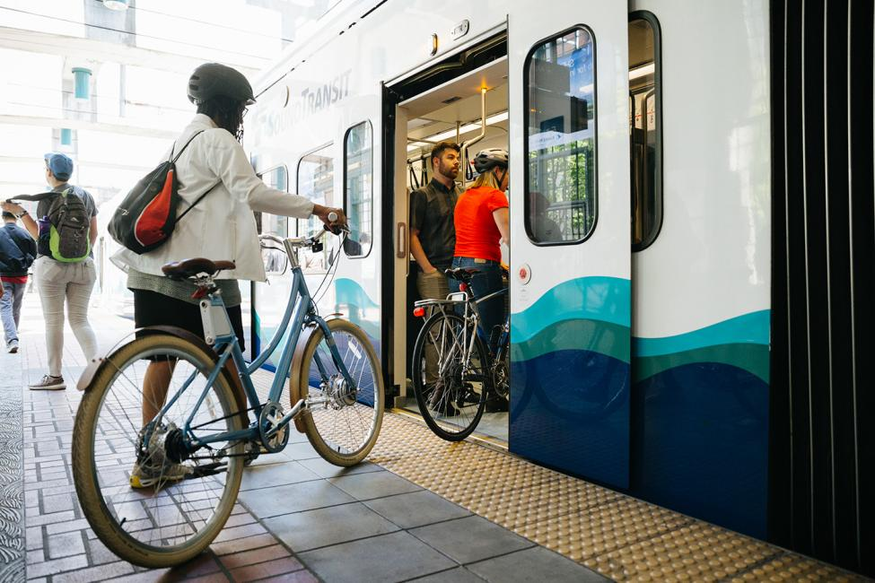 Tacoma Dome Link Extension Open house event header image, photo of bike rider boarding the train