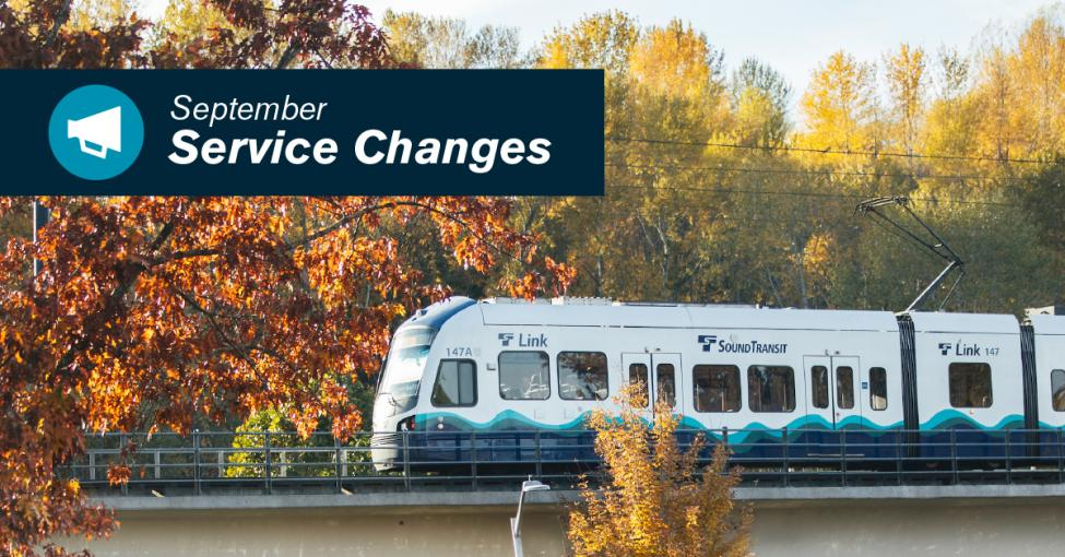 A link light rail train with fall foliage in the background