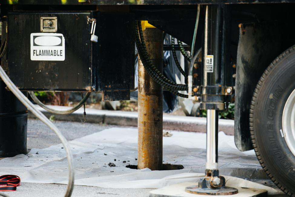A drilling rig is shown in a hole in the street in downtown Seattle.