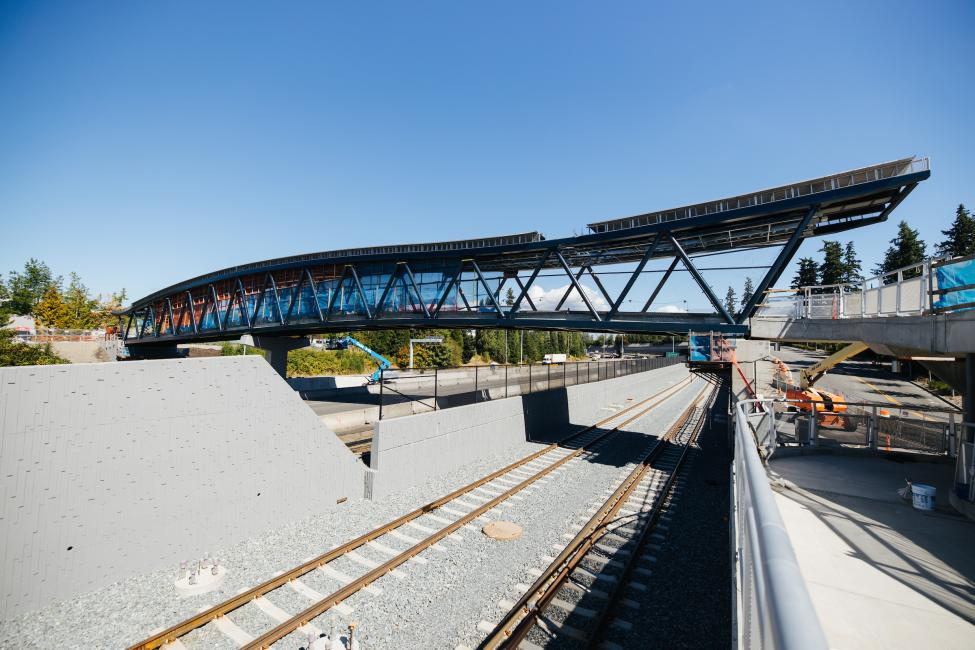 A new pedestrian bridge can be seen above SR-520 and train tracks connecting to Overlake Village Station.