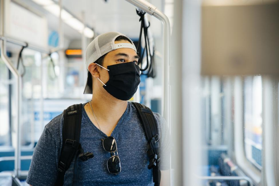 A man wearing a white backwards baseball hat and black face mask looks out the window of a Link train.