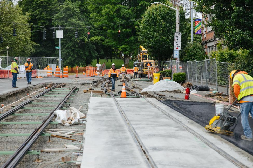Workers lay cement around new train tracks in the street for the Hilltop Tacoma Link Extension.
