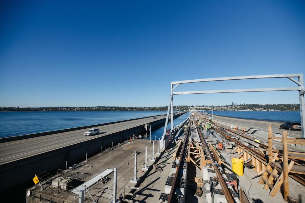 Light rail tracks are installed in the center lanes of the I-90 floating bridge, with Lake Washington visible on the left side of the photo.