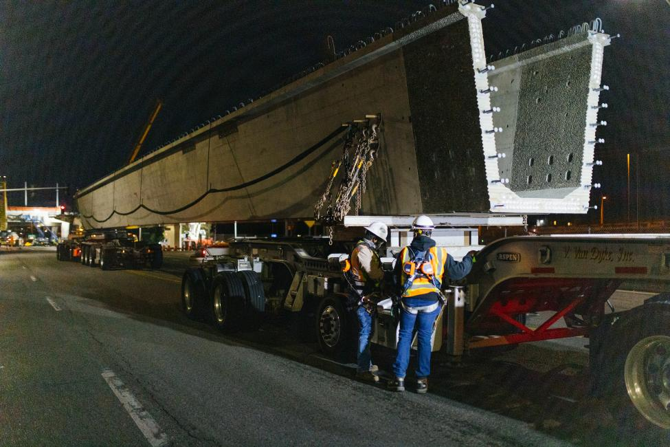 Workers stand next to a very large concrete girder span, sitting on a truck bed before getting ready to be lifted up.