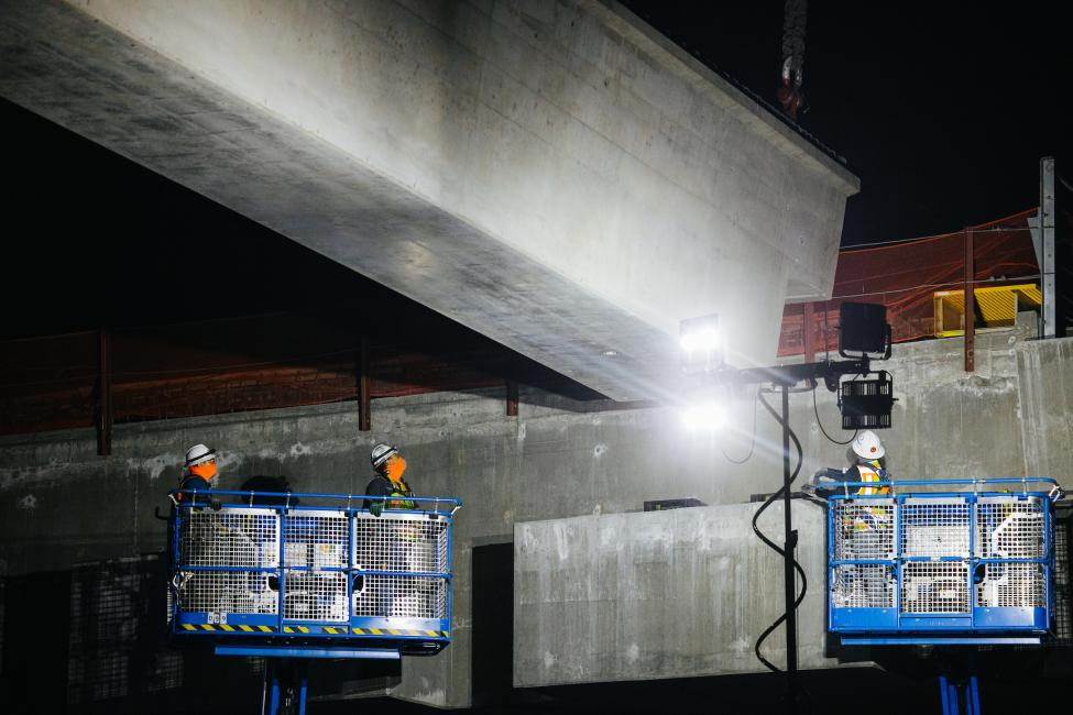 Three construction workers in lifts shine lights on the underside of a large concrete girder. Photo was taken at night.