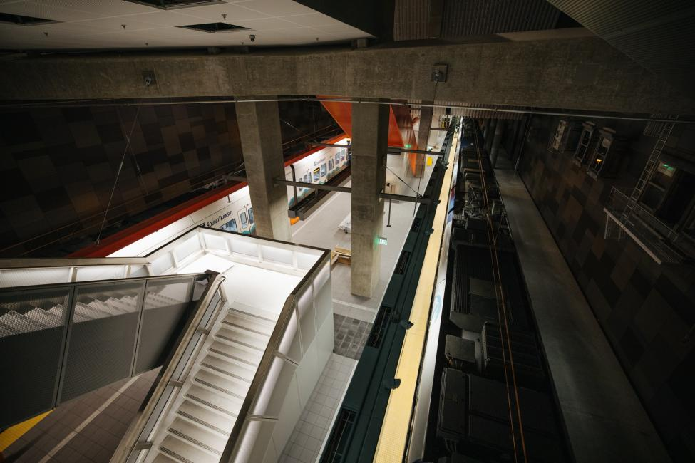 Looking down the stairs to the U District Station platform as trains roll through.