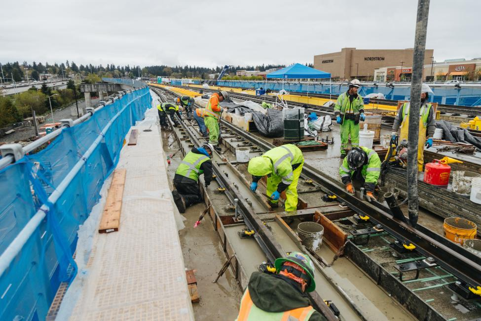 A half a dozen workers install rail on the elevated guideway near Northgate Station.
