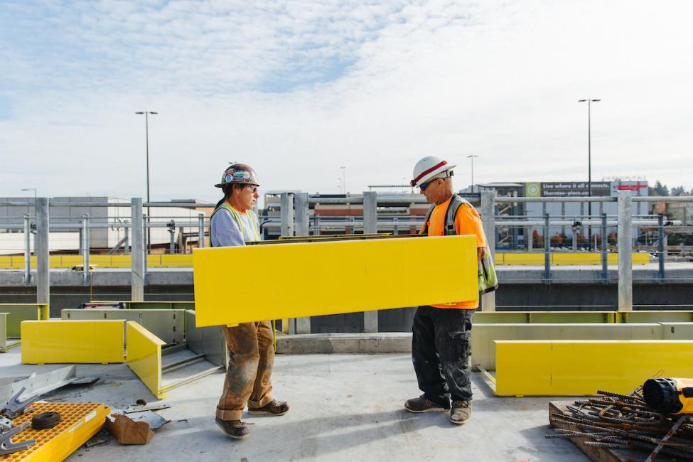 Workers carrying yellow panels on the platform of the future Northgate Link light rail station