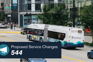 "A bus travels through downtown Seattle streets. A banner reads ""Proposed Service Changes - 544."""