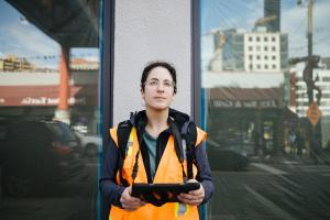 A woman in an orange vest holds a tablet while looking at buildings in Seattle's International District/Chinatown neighborhood.