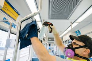 A worker cleans a Link light rail train with disinfectant.