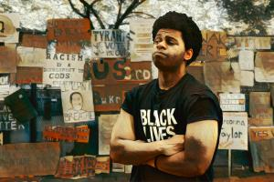Mural showing a young Black man wearing a Black Lives Matter t-shirt looking at a wall of anti-racism protest signs