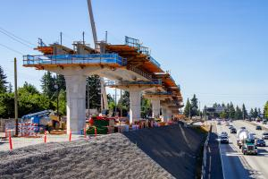 A light rail guideway is under construction next to I-5.