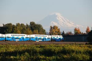 A Sounder train is pictured, with Mount Rainier in the background.