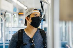 Photo of a rider wearing a mask, project update header image for West Seattle and Ballard Link Extensions