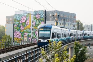A Link train travels along an elevated track in the Mt. Baker neighborhood, with a colorful mural of flowers visible on the side of a building in the background.