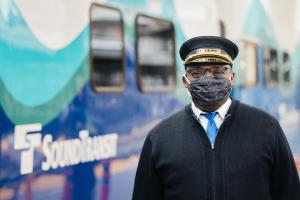 A man wearing a mask and conductor hat stands next to a Sounder train.