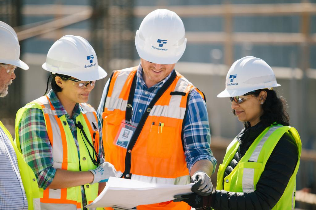 Four people in hard hats discuss a document out in the field.