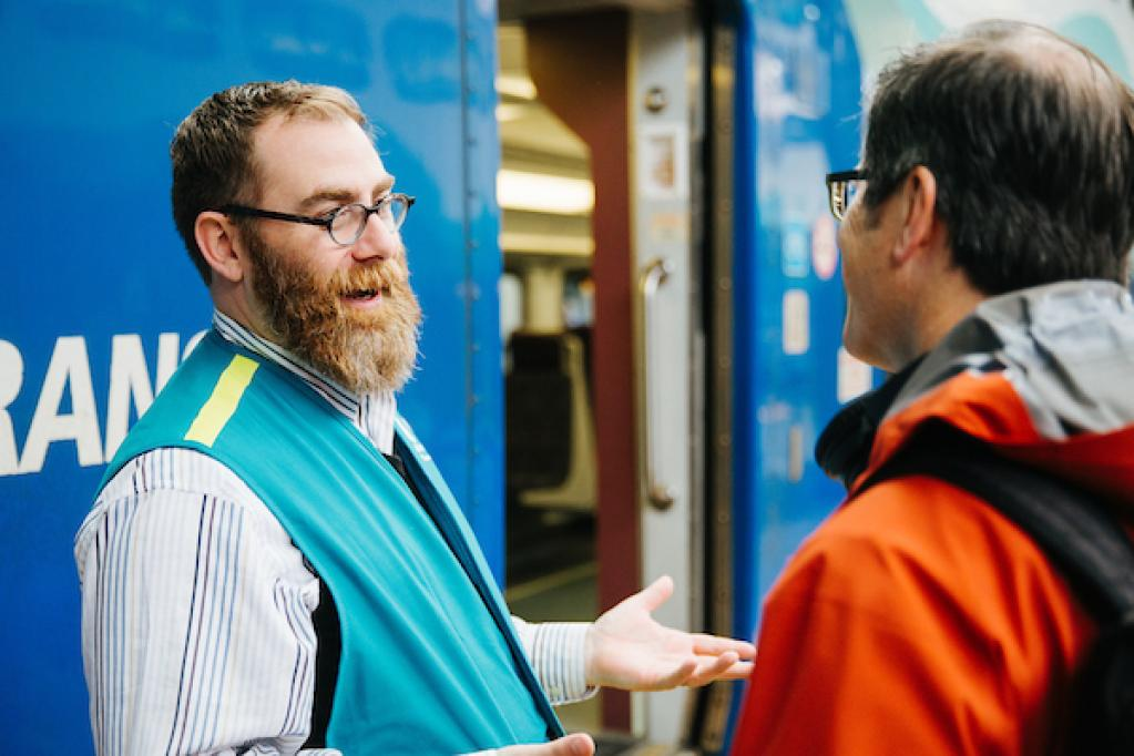 A man in a teal vest chats with another man by the door of a Sounder train.